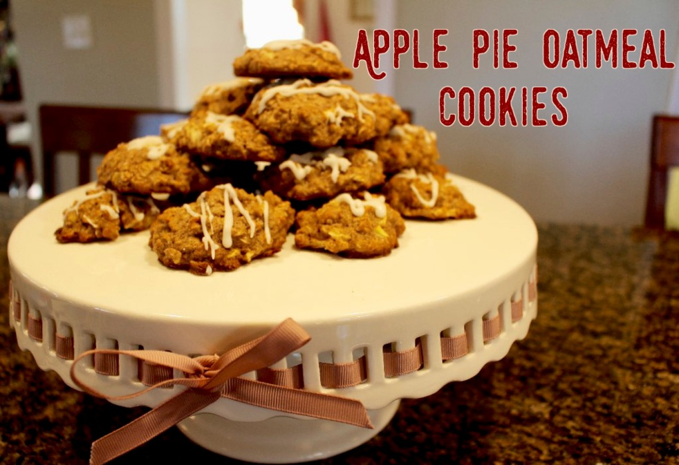 Apple pie oatmeal cookies stacked on top of a white cake plate